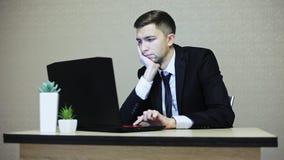 Uomo d'affari annoiato in vestito che lavora al computer portatile stock footage