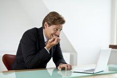 Uomo d'affari ansioso che esamina computer portatile Fotografia Stock