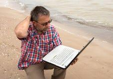 Uomo d'affari anziano che si siede con il taccuino sulla spiaggia Immagini Stock Libere da Diritti