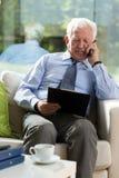 Uomo d'affari anziano che si siede in poltrona fotografia stock