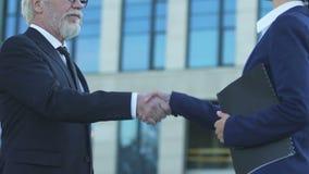 Uomo d'affari anziano che stringe le mani con il capo vendite, riuscito affare per la partenza stock footage