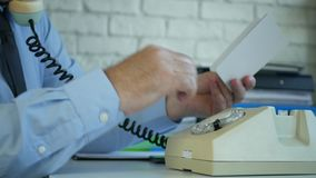 Uomo d'affari anziano nella stanza dell'ufficio facendo uso di vecchio telefono che compone un numero di telefono stock footage