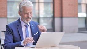 Uomo d'affari anziano stanco con funzionamento di dolore al collo sul computer portatile, all'aperto video d archivio