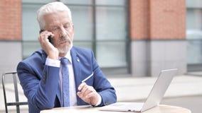 Uomo d'affari anziano Talking sul telefono, all'aperto video d archivio
