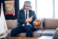 Uomo d'affari arabo che esamina globo con la lente di ingrandimento sullo strato la camera di albergo immagini stock libere da diritti