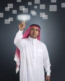 Uomo d'affari arabo che preme un tasto dello schermo attivabile al tatto Fotografia Stock Libera da Diritti