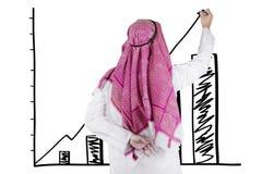 Uomo d'affari arabo che traccia grafico finanziario immagine stock libera da diritti