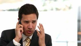Uomo d'affari arrabbiato che comunica sul telefono stock footage