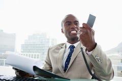 Uomo d'affari arrabbiato che esamina il suo microtelefono del telefono Fotografia Stock