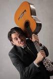 Uomo d'affari arrabbiato che prova a rompere la chitarra Fotografia Stock Libera da Diritti