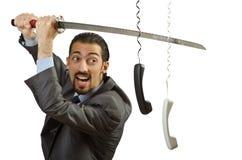 Uomo d'affari arrabbiato che taglia il cavo Fotografia Stock