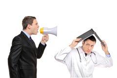 Uomo d'affari arrabbiato che urla ad un medico Immagini Stock Libere da Diritti