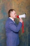 Uomo d'affari arrabbiato facendo uso del megafono sopra fondo grigio Fotografia Stock