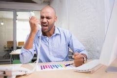 Uomo d'affari arrabbiato facendo uso del telefono allo scrittorio Fotografia Stock Libera da Diritti