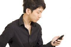 Uomo d'affari asiatico casuale che texting sul suo telefono delle cellule Fotografia Stock