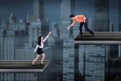 Uomo d'affari asiatico che aiuta una donna di affari Immagini Stock