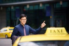 Uomo d'affari asiatico che chiama l'automobile del taxi che lascia lavoro Fotografia Stock