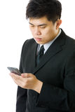 Uomo d'affari asiatico che esamina cellulare isolato Immagini Stock Libere da Diritti