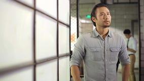 Uomo d'affari asiatico che guarda intorno al pensiero nel offie archivi video