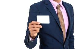 Uomo d'affari asiatico che mostra a mano carta in bianco su un backgrou bianco immagine stock