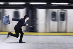 Uomo d'affari asiatico che precipita per un treno Immagini Stock