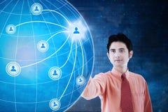 Uomo d'affari asiatico che preme l'icona della rete sociale Immagini Stock Libere da Diritti