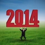 Uomo d'affari asiatico che solleva un nuovo anno 2014 Fotografia Stock