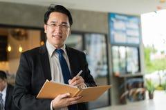 Uomo d'affari asiatico che tiene un libro e una penna per redigere un business plan Fotografia Stock Libera da Diritti