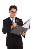 Uomo d'affari asiatico con i dati del controllo della lente d'ingrandimento in cartella Fotografie Stock