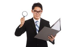 Uomo d'affari asiatico con i dati del controllo della lente d'ingrandimento in cartella Fotografia Stock