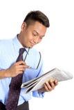 Uomo d'affari asiatico con i vetri che legge le notizie immagini stock