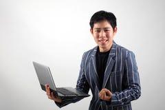 Uomo d'affari asiatico con il computer portatile Immagine Stock