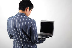 Uomo d'affari asiatico con il computer portatile Fotografia Stock