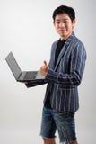 Uomo d'affari asiatico con il computer portatile Fotografie Stock