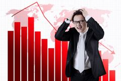 Uomo d'affari asiatico con il grafico diminuente di finanza Fotografia Stock