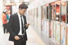 Uomo d'affari asiatico dei giovani pantaloni a vita bassa che utilizza smartphone mentre aspettando un treno nel sottopassaggio C fotografia stock