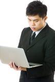 Uomo d'affari asiatico facendo uso del computer portatile Fotografia Stock
