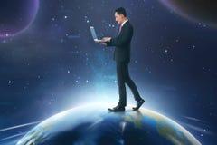 Uomo d'affari asiatico facendo uso del computer portatile mentre camminando sulla terra Fotografia Stock