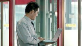 Uomo d'affari asiatico facendo uso del computer portatile nel corridoio