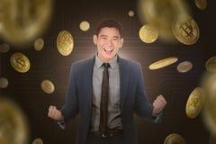 Uomo d'affari asiatico felice che sta sotto una pioggia del bitcoin Fotografia Stock Libera da Diritti