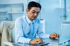 Uomo d'affari asiatico messo a fuoco facendo uso del calcolatore e del computer portatile Fotografia Stock Libera da Diritti