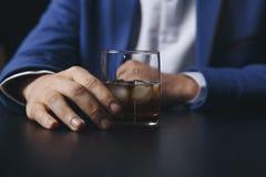 Uomo d'affari asiatico sollecitato che tiene un vetro di whiskey grafici di sonno e di dati lui, documento di affari alla scrivan fotografia stock