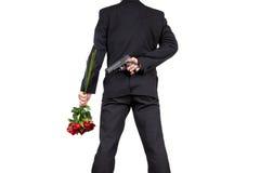 Uomo d'affari asiatico Standing con la tenuta del mazzo di Rose Flowers e nascondere pistola dietro il suo indietro Immagini Stock