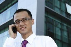 Uomo d'affari asiatico sul telefono Immagini Stock