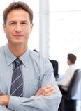 Uomo d'affari assertivo che si leva in piedi davanti al suo tè Fotografia Stock