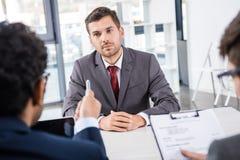 Uomo d'affari attento che ascolta i colleghi durante l'intervista di lavoro Fotografia Stock