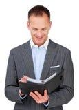 Uomo d'affari attraente che consulta il suo ordine del giorno Fotografia Stock