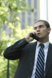 Uomo d'affari attraente che per mezzo del telefono delle cellule all'esterno Immagine Stock Libera da Diritti