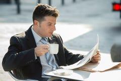 Uomo d'affari attraente che si siede all'aperto avendo tazza di caffè per le notizie del giornale della lettura di primo mattino  Immagini Stock