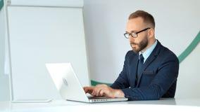 Uomo d'affari attraente nel funzionamento di vetro e del vestito con il computer portatile in ufficio bianco video d archivio